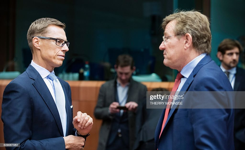 Finnish Finance Minister Alexander Stubb (L) talks to Belgian Finance Minister Johan Van Overtveldt (R) prior to a meeting of Eurogroup ministers at the European Council headquarters in Brussels on February 11, 2016. / AFP / THIERRY MONASSE
