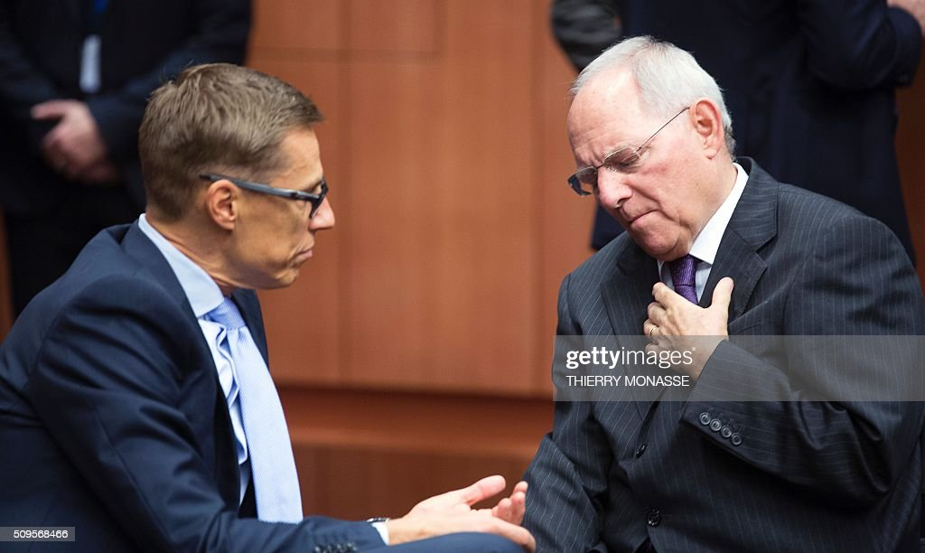 Finnish Finance Minister Alexander Stubb (L) talks to German Finance Minister Wolfgang Schäuble (R) prior to a meeting of Eurogroup ministers at the European Council headquarters in Brussels on February 11, 2016. / AFP / THIERRY MONASSE