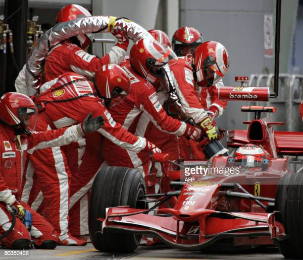 Finnish Formula One driver Kimi Raikkonen gets his Ferrari refueled during a pit stop at the Malaysian Formula One Grand Prix at the Sepang...