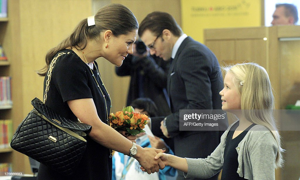 Finnish girl Saana Järvi (R) presents flowers to Crown Princess Victoria (L) in a library in Turku on September 20, 2011. The Swedish princess and her husband are on a two-day visit to Turku, the 2011 European Culture Capital.