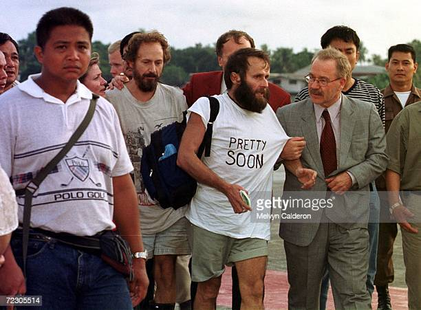 Finnish hostages Risto Vahanen and Seppo Fraenti are greeted by Finnish envoy Raimo Anttola upon their arrival at Zamboanga Philippines following...