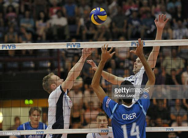 Finnish Mikko Esko and Matti Oivanen compete against Argentina's Pablo Crer during the World League volleyball match Finland vs Argentina on June 11...
