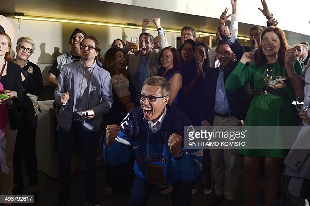 Finnish National Coalition Party's candidate Alexander Stubb celebrates at the European Parliament election event while watching the ice hockey gold...