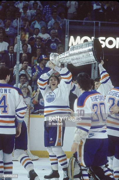 Finnish professional hockey player Jari Kurri of the Edmonton Oilers and Canadian colleague Craig Simpson hoist the Stanley Cup over their heads as...