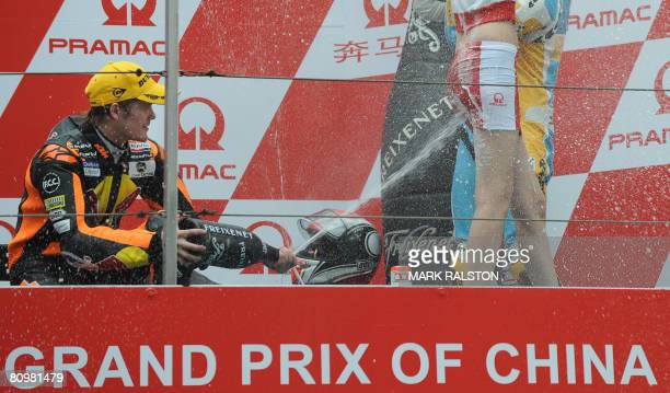 Finnish rider Mika Kallio from Team Red Bull KTM sprays champagne on a pit girl as he celebrates on the podium after winning the 250cc race at the...
