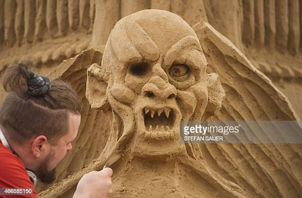 Finnish sand sculptor Pasi Ahokas carves a character from the movie 'Lord of the Rings' as preparations are under way for a sand sculpture festival...