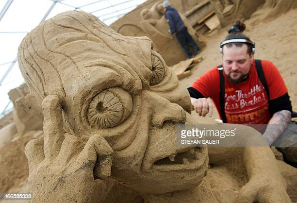 Finnish sand sculptor Pasi Ahokas carves the 'Gollum' character from the movie 'Lord of the Rings' as preparations are under way for a sand sculpture...