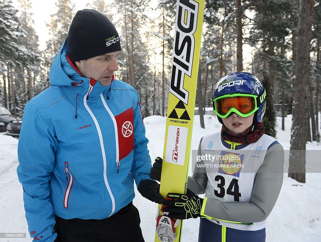 Finnish skijumper Janne Ahonen (L) poses for photographers with his son Mico at a ski jumping competition in Kouvola, Finland on January 12, 2013. Ski jumping legend Janne Ahonen plans to return to competition in 2013 as the Finnish star puts in a bid to win an Olympic individual medal at the 2014 Sochi Winter Olympics. OUT