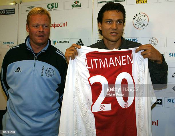 Finnish soccer player Jari Litmanen holds up his shirt of Ajax where he starts for a second contract as his coach Ronald Koeman stands next to him...