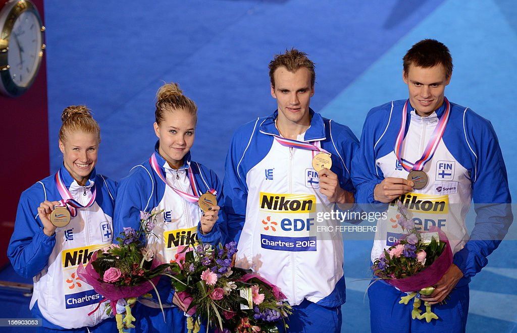 Finnish swimmers Hanna-Maria Seppala (L), Laura Kurki (2nd L), Andrei Tuomola (2nd R) and Ari-Pekka Liukkonen pose with their medals after winning the bronze in the mixed 4X50m freestyle final at the European Swimming Championships on November 24, 2012, in Chartres.