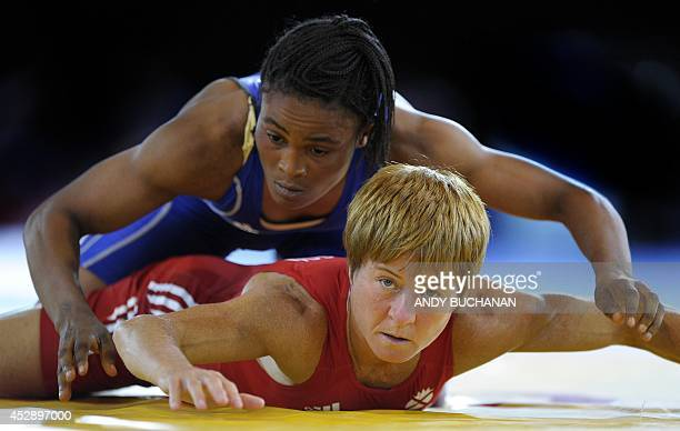 Fiona Robertson of Scotland takes on Rebecca Muambo of Cameroon in the Women's Freestyle 48kg Freestyle Wrestling competition at the 2014...