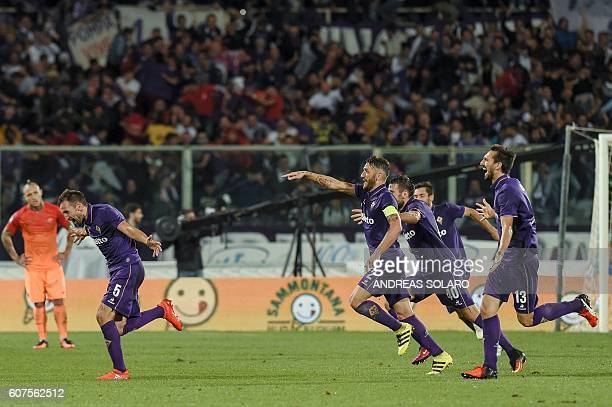 Fiorentina's midfielder from Croatia Milan Badelj celebrates with his team mates after scoring against AS Roma during the Italian Serie A football...