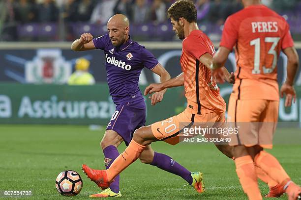Fiorentina's midfielder from Spain Borja Valero fights for the ball against AS Roma's defender from Argentina Federico Fazio during the Italian Serie...