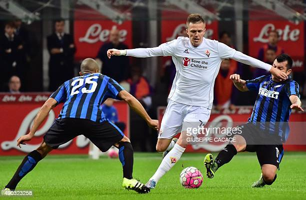 Fiorentina's Slovenian midfielder Josip Ilicic vies for the ball with Inter Milan's Brazilian defender Joao Miranda and Inter Milan's Chilean...