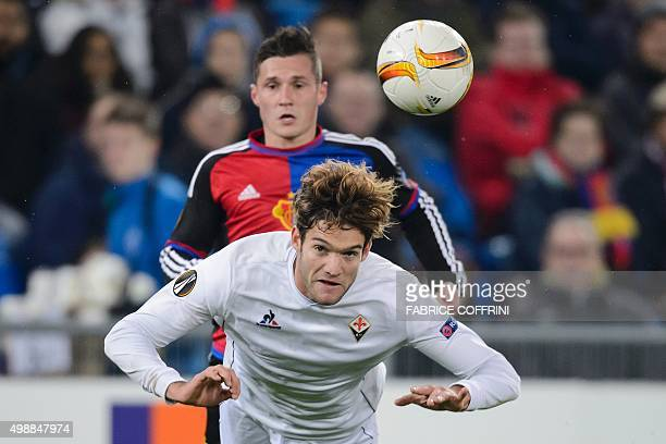 Fiorentina's Spanish defender Marcos Alonso Mendoza heads the ball in front of Basel's Swiss midfielder Taulant Xhaka during the UEFA Europa League...
