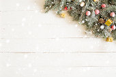 Fir branch with Christmas decorations on the white wooden table or plank background.