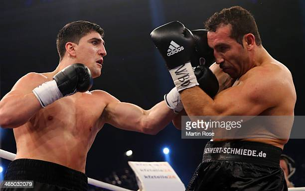 Firat Arslan of Germany exchanges punches with Marco Huck of Germany during their WBO Cruiserweight title fight at HansMartinSchleierHalle on January...