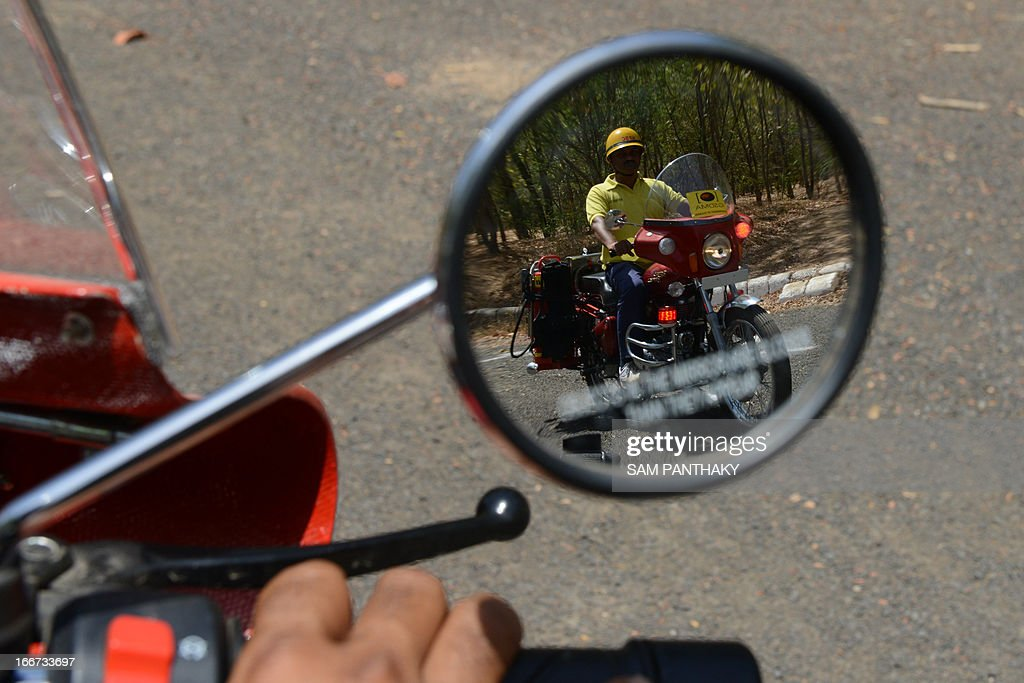Fire and Rescue Instructor Gajendrabhai Chauhan from the Ahmedabad Fire and Emergency Services is pictured in the rear view mirrow of a Motorcycle Mounted Fire Fighting unit as he rides in Ahmedabad on April 16, 2013. Some 29 of these motorcycles, based on the 350cc Enfield Bullet, will be dispatched across the state for first responders in remote, wooded, and urban areas. AFP PHOTO / Sam PANTHAKY