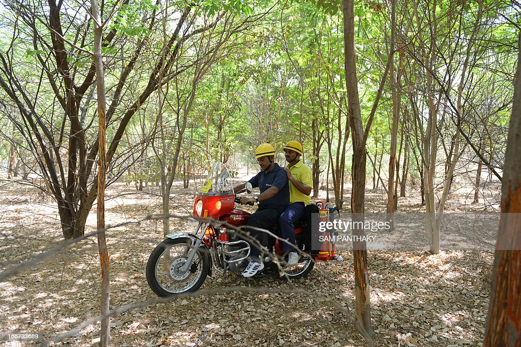Fire and Rescue Instructor Jayantibhai Vavdiya (C) from the Ahmedabad Fire and Emergency Services demonstrates the Motorcycle Mounted Fire Fighting unit as he rides in a forested area in Ahmedabad on April 16, 2013. Some 29 of these motorcycles, based on the 350cc Enfield Bullet, will be dispatched across the state for first responders in remote, wooded, and urban areas. AFP PHOTO / Sam PANTHAKY
