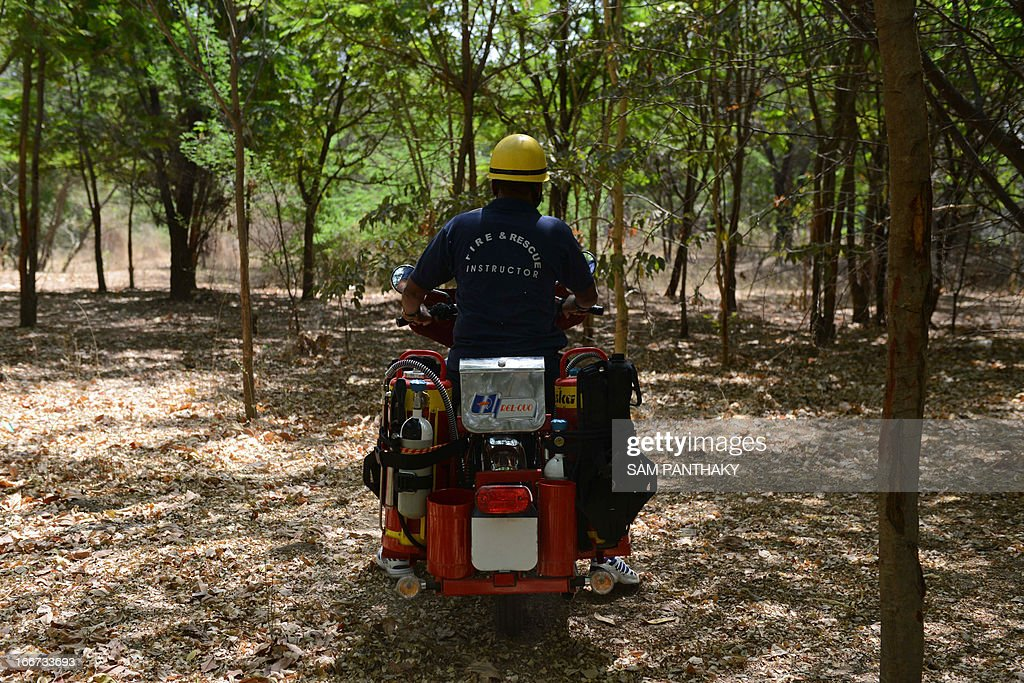 Fire and Rescue Instructor Jayantibhai Vavdiya from the Ahmedabad Fire and Emergency Services demonstrates the Motorcycle Mounted Fire Fighting unit as he rides in a forested area in Ahmedabad on April 16, 2013. Some 29 of these motorcycles, based on the 350cc Enfield Bullet, will be dispatched across the state for first responders in remote, wooded, and urban areas. AFP PHOTO / Sam PANTHAKY