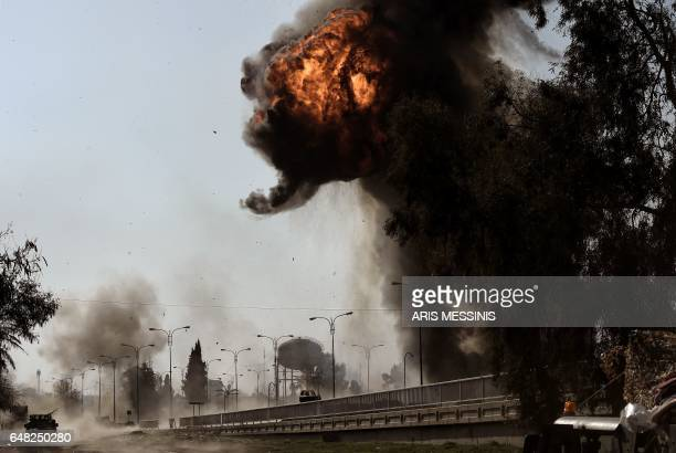 TOPSHOT Fire and smoke billow following a car bomb explosion as Iraqi forces clash with Islamic State group fighters in Mosul on March 5 during an...