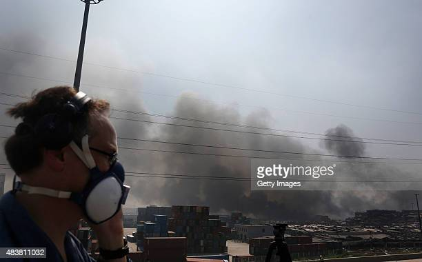 Fire and smoke continues to rise at the site of a massive explosion at a warehouse in the Binhai New Area on August 13 2015 in Tianjin China At least...