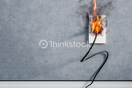 fire and smoke on electric wire plug in indoor, electric short circuit causing fire on plug socket : Stock Photo