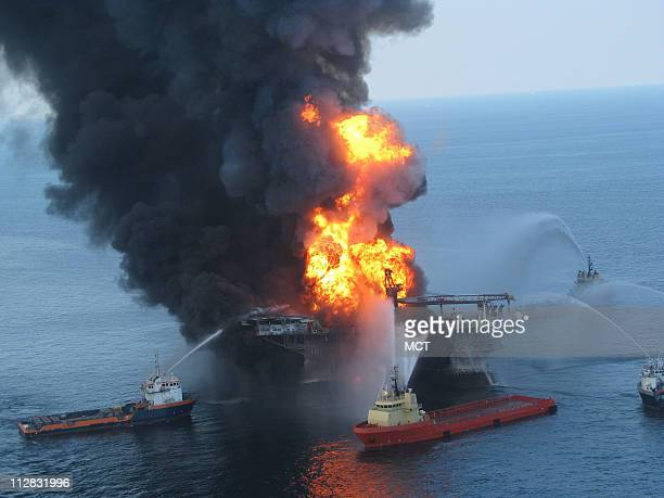 Fire boat response crews battle the blazing remnants of the off shore oil rig Deepwater Horizon April 21 2010 A Coast Guard MH65C dolphin rescue...