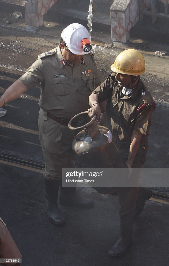 Fire brigade personnel bring out a gas cylinder from the incident place after fire engulfed a multi-storey market complex at Sealdah on February 27, 2013 in Kolkata, India. At least 19 people were killed in it. A dozen people were also critically injured in the fire that broke out at about 3 am at Sealdah in Central Kolkata, when many victims (Labours & shop keepers) were asleep. Even as 26 fire tenders battled the leaping flames and firemen scrambled to rescue people, many were feared trapped inside the market that houses plastic items, thermocol and paper godowns.