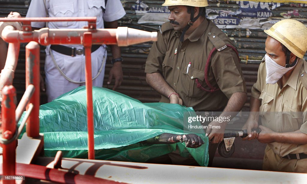 Fire brigade personnel bring out dead body from the incident place after fire engulfed a multi-storey market complex at Sealdah on February 27, 2013 in Kolkata, India. At least 19 people were killed in it. A dozen people were also critically injured in the fire that broke out at about 3 am at Sealdah in Central Kolkata, when many victims (Labours & shop keepers) were asleep. Even as 26 fire tenders battled the leaping flames and firemen scrambled to rescue people, many were feared trapped inside the market that houses plastic items, thermocol and paper godowns.