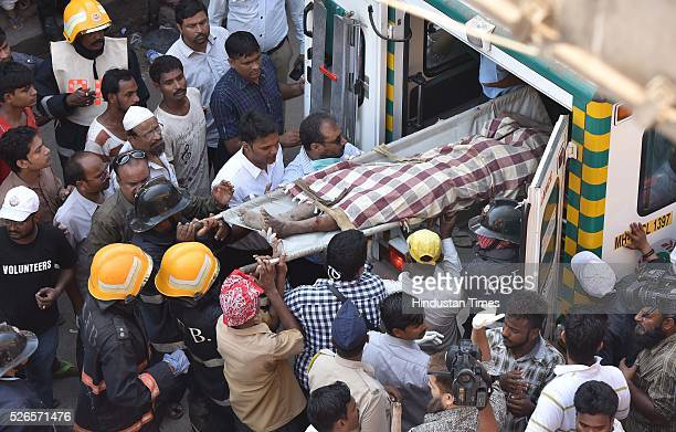 Fire brigade personnel put the dead body into ambulance removed from debris of building collapse at lane number 14 of Kamathipura on April 30 2016 in...