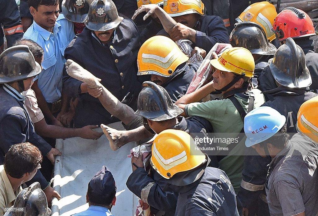 Fire brigade personnel remove dead body from debris of building collapse at lane number 14 of Kamathipura, on April 30, 2016 in Mumbai, India. At least five people were killed and several others were injured when a section of a two-storey building collapsed in Kamathipura area. Many people had found themselves trapped in the mangled remains of the structure after a section of the building collapsed.