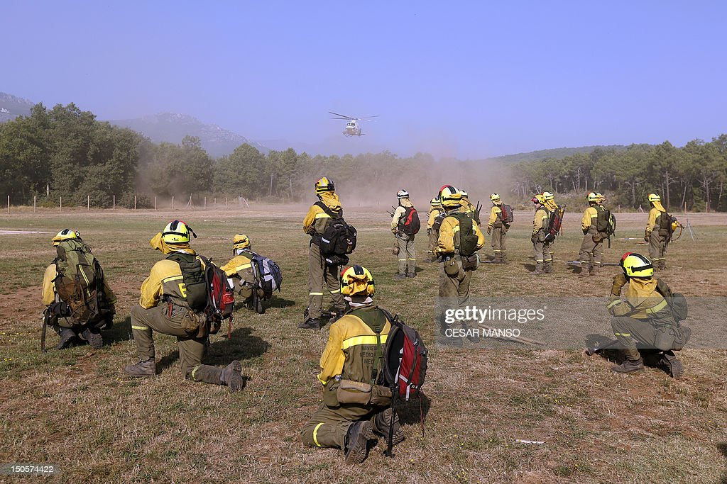 Fire Brigade reinforcement wait to be airlifted by helicopters to the wildfire in Tabuyo del Monte, near Leon on August 21, 2012. Spain's government Thursday denied crisis budget cuts had hit national resources for fighting this summer's spate of deadly wildfires. Numerous wildfires have broken out across Spain including a fire that has ravaged thousands of hectares on the Spanish island of La Gomera, part of the Canary Islands archipelago, in the sweltering heat in recent weeksAFP PHOTO/CESAR MANSO