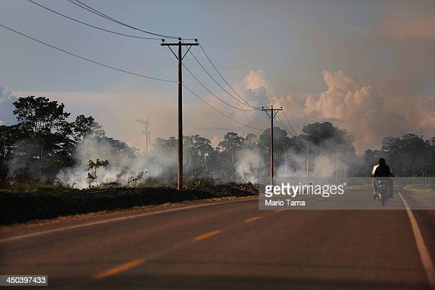 Fire burns in a deforested section along the Interoceanic Highway in the Amazon lowlands on November 16 2013 in Madre de Dios region Peru The...