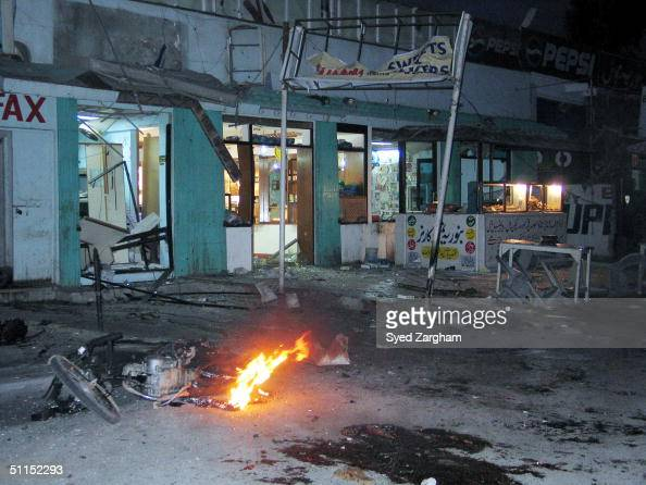 Fire burns in the wreckage of a motorcycle after a bombing August 8 2004 in Karachi Pakistan Two bombs exploded within minutes of each other near an...