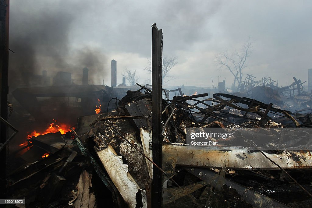 Fire burns near destroyed homes and businesses following Hurricane Sandy on October 30, 2012 in the Rockaway section of the Queens borough of New York City. At least 40 people were reportedly killed in the U.S. by Sandy as millions of people in the eastern United States have awoken to widespread power outages, flooded homes and downed trees. New York City was hit especially hard with wide spread power outages and significant flooding in parts of the city.