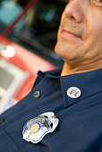 Fire captain with badge standing near fire engine (selective focus)