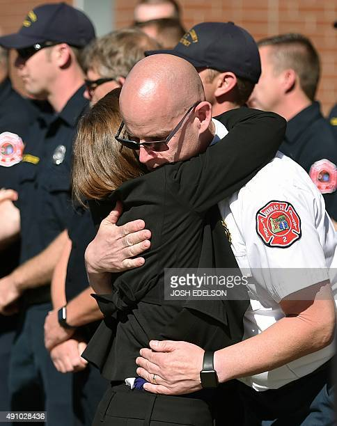 Fire Chief and first responder Greg Marlar receives a hug from Oregon Governor Kate Brown at the conclusion of a press conference in Roseburg Oregon...