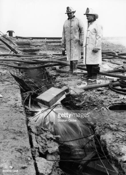 Fire Chief John R Green left and Ed S Galighan right examine the damage done at the pier on Castle Island after a fouralarm fire in Boston Dec 2 1961