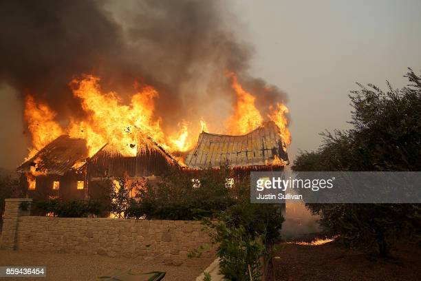 Fire consumes a barn as an out of control wildfire moves through the area on October 9 2017 in Glen Ellen California Tens of thousands of acres and...