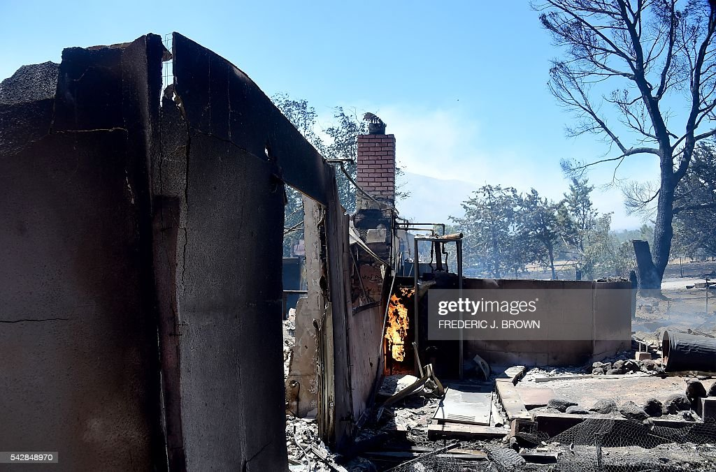 A fire continues burning amid a demolished home in the community of Squirrel Valley in Lake Isabella, California on June 24, 2016. An intense wildfire broke out yesterday afternoon scorched dozens of homes and structures in this mountainous community northeast of Bakersfield in Kern County. / AFP / FREDERIC