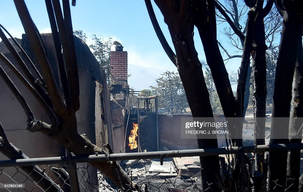 A fire continues burning amid the rubble of a demolished home in the community of Squirrel Valley in Lake Isabella, California on June 24, 2016. An intense wildfire broke out yesterday afternoon scorched dozens of homes and structures in this mountainous community northeast of Bakersfield in Kern County. / AFP / FREDERIC