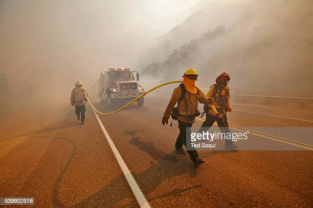 A fire crew walks up Grimes Canyon with a foam truck putting out spot fires on the sides of the road 9000 acre Guiberson wildfire burns out of...