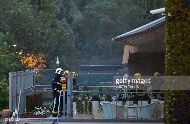 Fire crews stand outside a balcony attached to Centre Court following a fire alert and evacuation on day three of the 2015 Wimbledon Championships at...