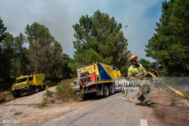 Fire crews work to try and extinguish a wildfire along the CV A9 road near Yeste in south eastern Spain on July 27 2017 Fires ravaged bone dry pine...
