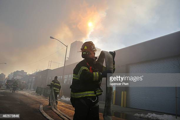 Fire Department of New York firefighters work to contain a building fire that went to six alarms at the CitiStorage warehouse building at 5 North...