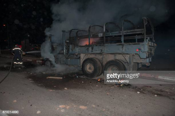Fire department workers extinguish a vehicle belongs to Kingdom of Morocco's Gendarmerie in Al Hoceima Morocco on July 21 2017 Protesters continues...