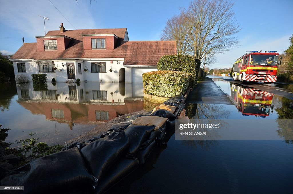 A fire engine drives past a flooded property in Wraysbury west of London, on February 13, 2014. Hurricane-force winds from an Atlantic storm left tens of thousands of Britons without power Thursday and one man dead, adding to the misery after devastating floods caused by the wettest winter in 250 years.