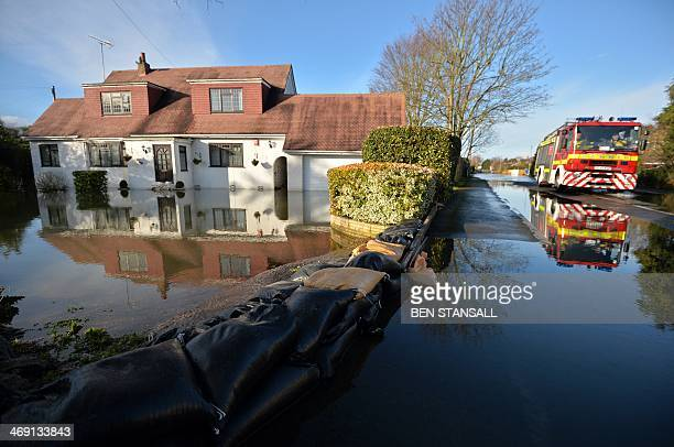 A fire engine drives past a flooded property in Wraysbury west of London on February 13 2014 Hurricaneforce winds from an Atlantic storm left tens of...