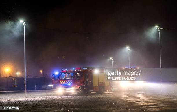 Fire engines are stationed at the still smouldering GrandeSynthe migrant camp early April 11 2017 outside the northern French city of Dunkirk after a...